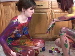 Lavender Rayne and Indigo Augustine playing surrounding paint